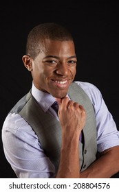 Black businessman in vest and tie,, with his hand on his chin smiling broadly