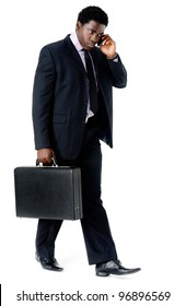 Black businessman walking and talking on his phone