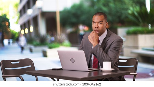 A black businessman works on his laptop while sipping coffee