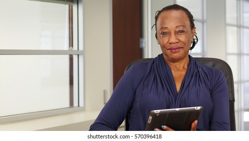 A black businesswoman happily uses her tablet while posing for a portrait