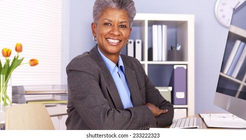 Black businesswoman sitting at desk smiling