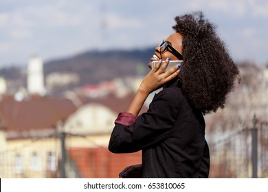 Black businesswoman talking on the phone and smiling. Great city view.
