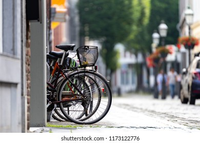 Black bycicles parked on the street with blurry background