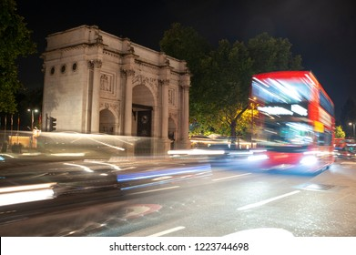 Black cab and double decker buses drive past Marble Arch at night in London.