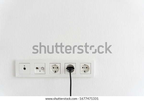 black cable cord pluged in receptacle of modern electric socket in multi paneling, internet, tv or radio adapter socket on white wall background at hom