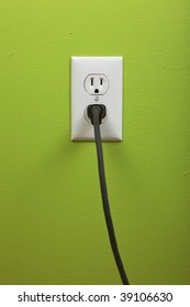 black cable plugged in a white electric outlet mounted on green wall