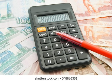 black calculator, different Russian banknotes and pen