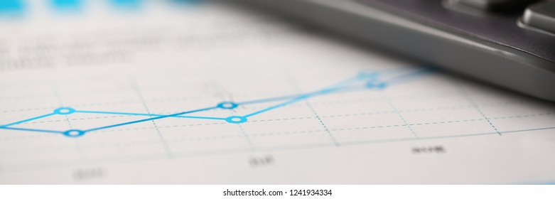Black calculator and financial graph paper statistics form lie at office table closeup. Count loan and credit price sale form review irs investigation progress assessment information letterbox