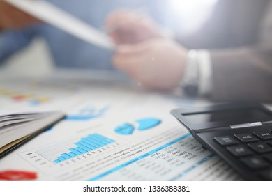 Black calculator and financial statistics on clipboard pad at office table closeup. Internal Revenue Service inspector sum check irs investigation earnings savings loan and credit concept