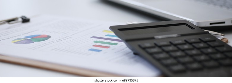 Black calculator and financial statistics on clipboard pad at office table closeup. Internal Revenue Service inspector sum check, irs investigation, earnings, savings, loan and credit concept