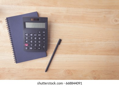 black calculator on notebook paper with pen on wood table