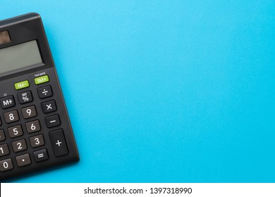 Black calculator on solid blue background with copy space using for financial activity, accounting, tax calculation or saving and investment.