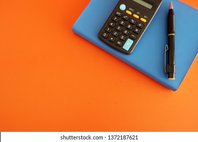 A  black calculator and a pen on blue notebook , on orange background with copy space. Concept of money planning, financial management,business planning