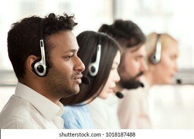 Black call center operator with colleagues. Side view of line of call centre employees are smiling and working on computers.