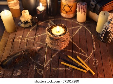 Black candle in the circle with pentagram and magic candles on old table. Black magic ritual with occult, evil and esoteric symbols. Scary halloween rite