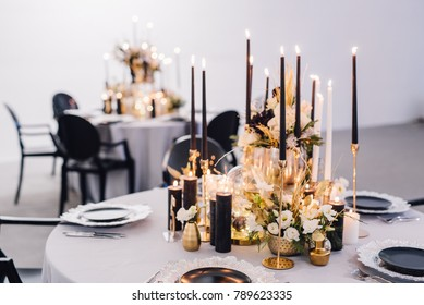 Black candles on candlesticks with flowers in vases on reception table. Wedding. Decor