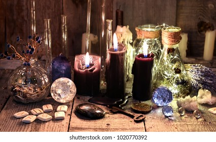 Black candles with runes, crystals, healing herbs and ritual objects. Occult, esoteric and divination concept.
