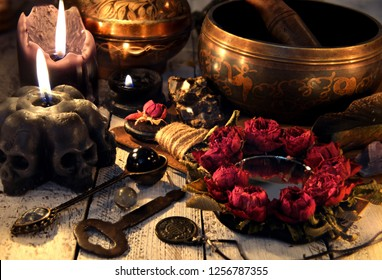 Black candles with skulls, rose mirror, metal key and singing bowl on witch table. Magic ritual. Wicca, esoteric and occult background with vintage witch objects