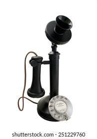"Black candlestick telephone with metal dial. A 1920s vintage phone with the ear-piece on the hook. The information disc at the centre of the dial has the instructions ""To call long distance dial 0""."
