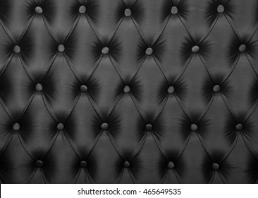 Black capitone textile background, retro Chesterfield style checkered soft tufted fabric furniture diamond pattern decoration with buttons, close up
