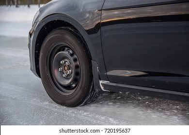 Black car accelerates on absolutely frozen iced road surface. No asphalt, no tarmac under the wheel. Clean and clear ice under the wheel. Studded winter tyres are in action.