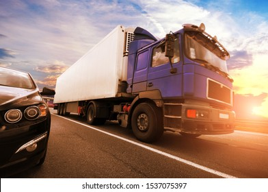A black car with a big blue truck and white trailer with space for text on the countryside road against a sky with a sunset