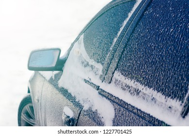Black car covered with frozen rain in winter