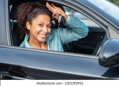 Black car driver woman smiling showing new car keys and car