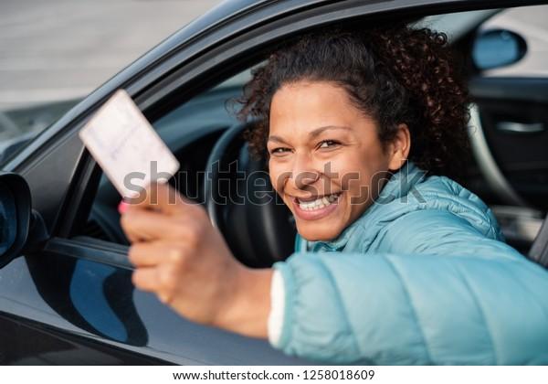 Schwarze Autofahrerin lächelnd mit neuen Führerscheinen