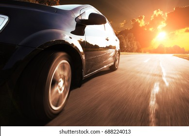 Black car driving fast on a road against blue sky in the countryside with sunset