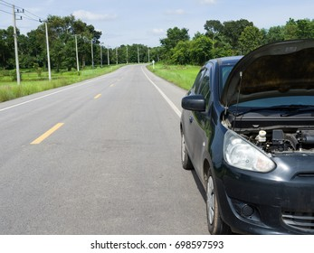 Black car has problems on the street in countryside