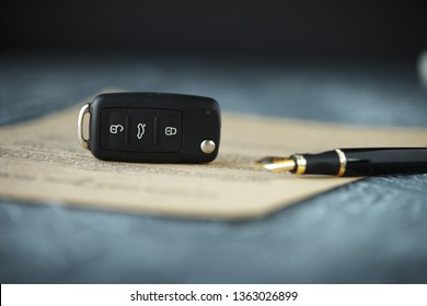 Black car key and money on a signed contract of car sale.