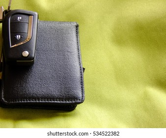 Black Car Keys with small Pendant on top of black Wallet in greenish Textile Background