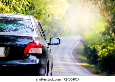 Black car on beautiful way with the background of the road to forest and mountain. season car trip road travel concept.select focus on rearview mirror car,cinematic photography film grain tone style