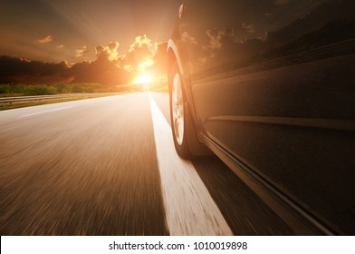 Black car on the countryside road driving fast against dark night sky and sunset