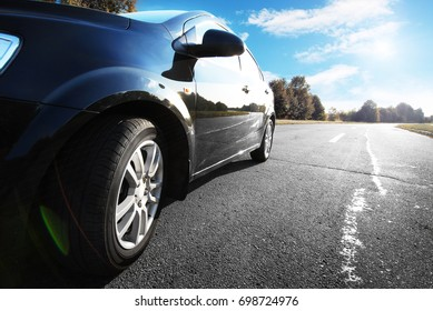 Black car on a road against blue sky in the countryside
