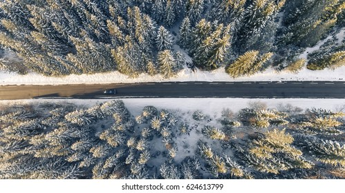 Black car on road in beautiful winter scenery, from a drone.