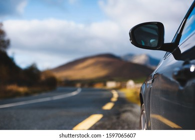 black car on road at mountain in ireland