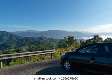 black car parked on the side od road with beautiful green mountains and valley in morning