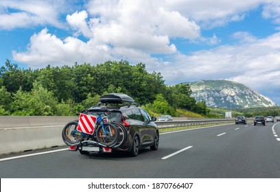 Black car with roof luggage box and trunk bike rack driving on the highway. Beautiful mountain landscape background