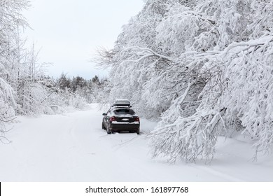 Black car standing on winter country road on roadside