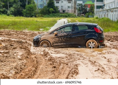 The black car stuck in the mud. Can not fall out of the mud