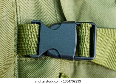 black carbine latch on the harness on the green matter of the backpack