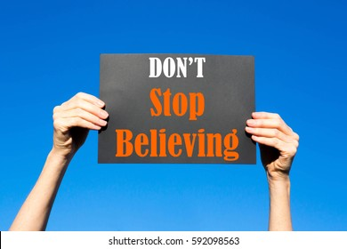 Black card placard with the concept of Don't Stop Believing against a clear blue sky background