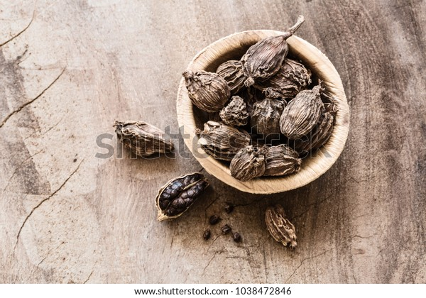 Black cardamom whole seeds in a bowl on wooden background indian spice with copyspace top view