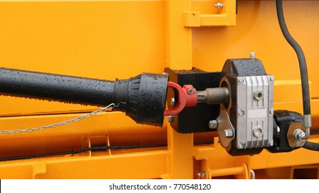 A black cardan shaft with a hinge is attached to the reducer against the background of the yellow metal case. Cardan drive grain harvester.