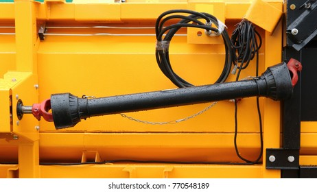 Black cardan shaft with two hinges on the background of a yellow metal case. Cardan drive grain harvester.