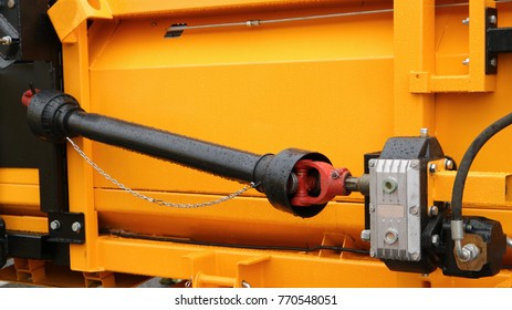 A black cardan shaft with two cardan joints is attached to the reducer against the background of a yellow metal case. Cardan drive grain harvester.