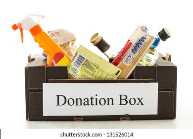 Black cardboard donation box with houseware product and food on white background