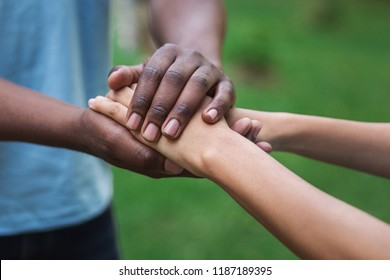 Black caregiver supporting woman, holding her hand outdoors. Philanthropy, kindness, volunteering concept, copy space